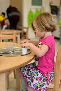 Kayla Warden, age 3,  concentrates on magnet work.