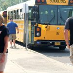 School buses drop staff off for rally